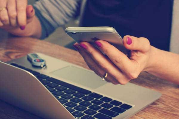 Frau mit Smartphone und Laptop